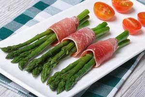 espargos verdes envolto em presunto em uma vista superior do prato foto