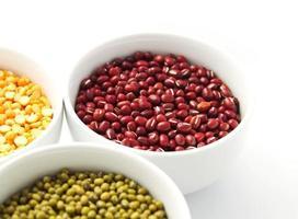 tigelas brancas de mung, feijão vermelho e ervilhas amarelas foto