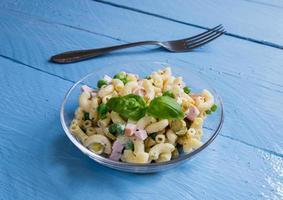 salada de macarrão em uma tigela de vidro em madeira azul foto