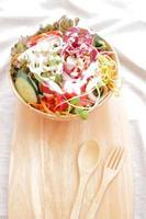 salada com creme em uma tigela de madeira foto