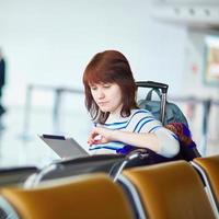 jovem passageiro no aeroporto, usando seu tablet foto