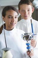 menina sorridente, segurando o troféu de esgrima