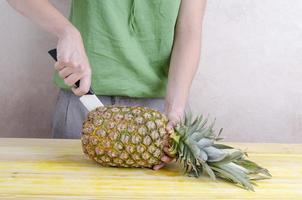 mulher cortando um abacaxi sobre madeira.