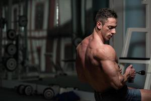 jovem macho fazendo exercícios nas costas no ginásio foto