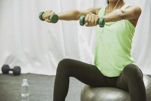 mulher levantar peso enquanto está sentado foto