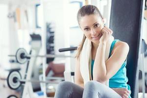 mulher sorridente na academia relaxante no banco de exercício foto