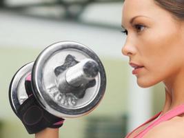 close-up do rosto de mulher com halteres no ginásio foto