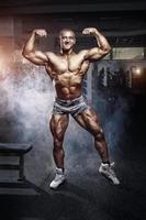homem fisiculturista posando no ginásio foto