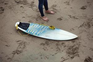 prancha de surf na praia ao lado das pernas do surfista.