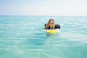 mulher com uma prancha de surf no oceano foto
