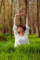 menina jovem fazendo yoga em uma grama verde foto