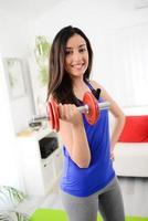 alegre jovem morena fazendo exercícios de fitness em casa