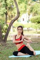jovem mulher bonita fazendo exercícios de ioga no parque foto