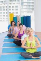 mulheres meditando na aula de fitness foto