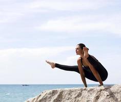 mulher de ioga posa na praia perto do mar e pedras. phuket foto
