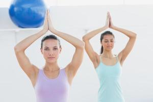 desportivas mulheres com as mãos unidas no estúdio de fitness foto