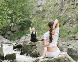mulher e homem fazendo yoga na natureza foto