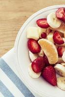 salada de frutas em fundo de madeira foto