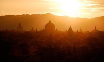 vista panorâmica do sol de silhuetas de templos antigos em bagan, myan foto