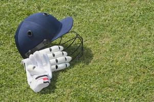 capacete de críquete e luvas de batedura em um campo foto