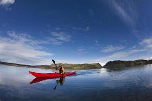 homem remar canoa no lago ainda foto