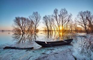 paisagem de primavera com barco de madeira foto