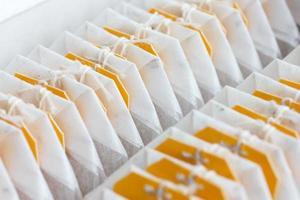 saquinhos de chá com a etiqueta amarela embalados em uma linha. foto