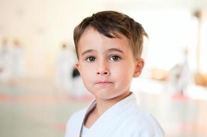 retrato de menino karatê treinando no salão de esporte foto
