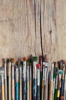 linha de pincéis de artista na mesa de madeira velha foto