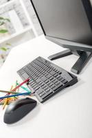 computador com teclado, mouse e lápis foto