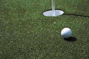 bola de golfe e buraco em um campo foto