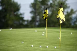 putting green com foco seletivo de bolas de golfe e bandeira foto