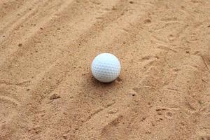 bola de golfe na areia foto