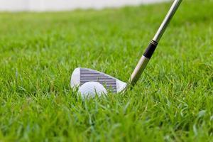bola de golfe e ferro na grama alta foto