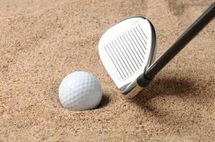 bola de golfe na armadilha de areia foto