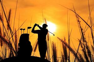 golfista silhueta lindo céu retroiluminado fundo por do sol foto