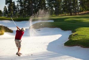 explosão de bunker pelo jogador de golfe caucasiano sênior foto