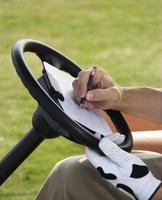 homem marcando golfe foto