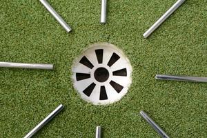 eixos de aço de golfe apontando para o buraco de golfe foto