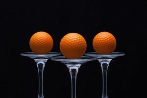 três copos de champanhe e bolas de golfe foto