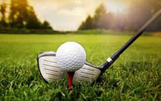 taco de golfe e bola na grama foto
