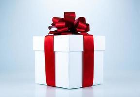 caixa de presente branca com fita vermelha e arco