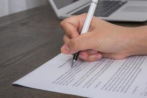 close-up de mão preenchendo um formulário de pedido de emprego foto