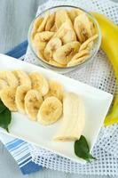 fatias de banana fresca e seca em fundo de madeira foto
