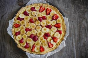 torta de bananas e morangos foto