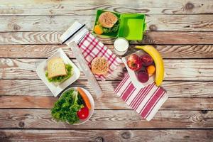 almoço escolar com sanduíche, leite e frutas, na mesa de madeira foto