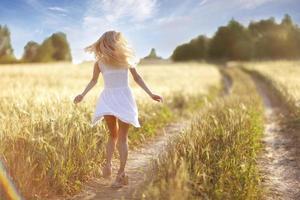 garota feliz na estrada em um campo de trigo foto