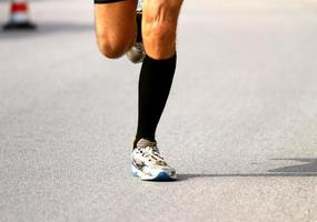 corredor rápido com tênis durante a maratona na estrada foto