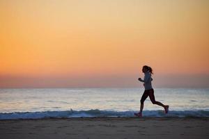 mulher de aptidão correndo na praia