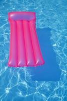 cama de ar rosa flutuando na piscina foto